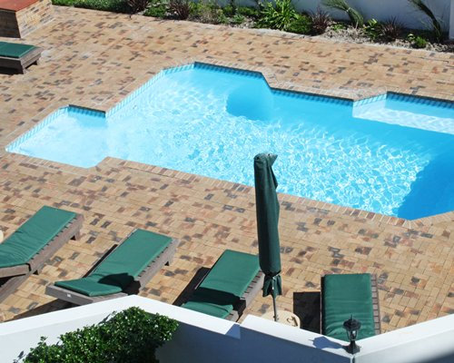 Outdoor swimming pool with chaise lounge chairs and sunshade.