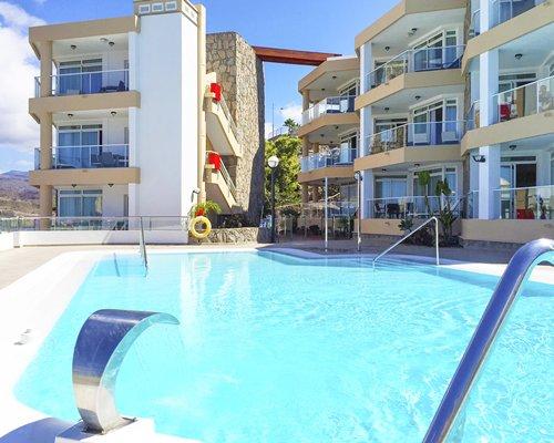 Outdoor swimming pool alongside multiple unit balconies.