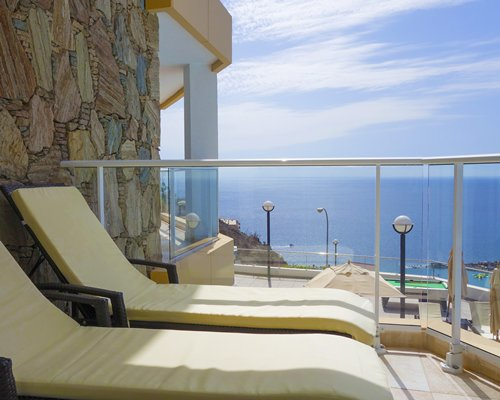 Balcony with chaise lounge chairs and ocean view.