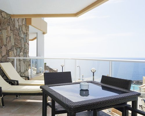 A balcony with chaise lounge chair and patio furniture alongside the ocean.