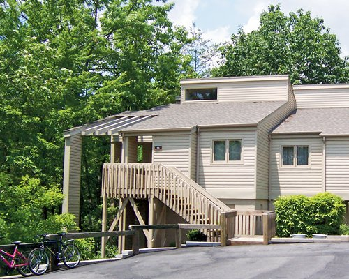 Exterior view of a unit at Foxrun Townhouses with a stairway and bikes surrounded by wooded area.