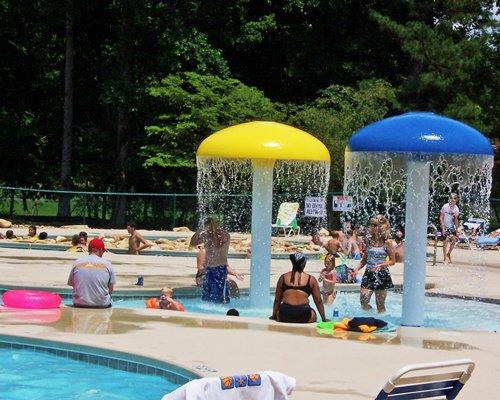 Group of people enjoying in an outdoor swimming pool with raining mushroom umbrella.