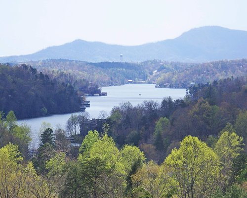 View of the lake surrounded by wooded area alongside the mountains.