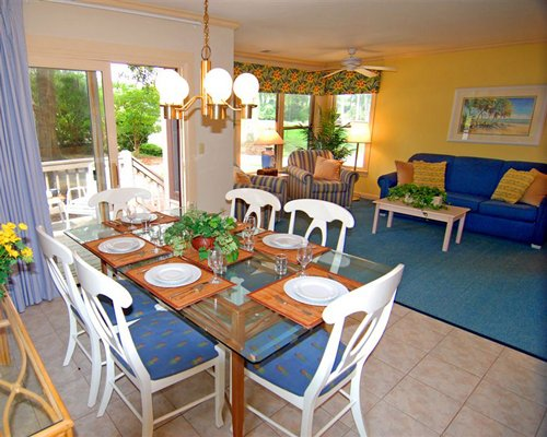 A well furnished living room with dining area outdoor patio and patio chairs.