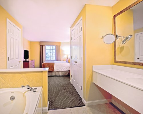 A bathroom with bathtub and single sink vanity alongside a bedroom.
