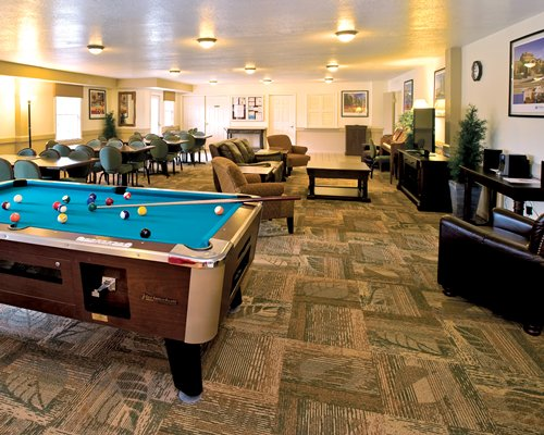 An indoor recreational room with pool table and television.