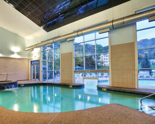 An indoor swimming pool with a water feature and outside view.
