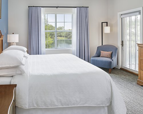 A well furnished bedroom with queen bed television and outside view.