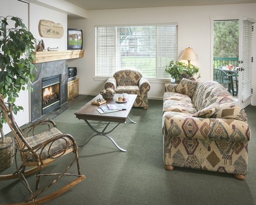 A well furnished living room with fire in the fireplace television outdoor patio and patio chairs.