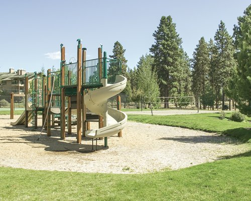 Kids playscape alongside outdoor recreation area with volleyball net surrounded by wooded area.