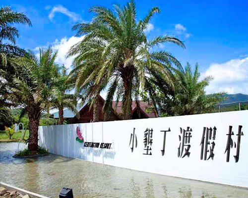 A view of the resort name engraved in the wall with palm trees.