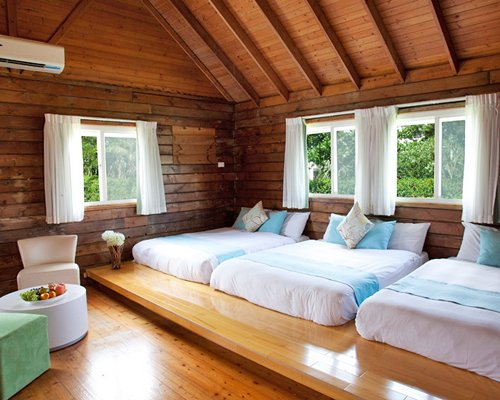 A well furnished bedroom with three beds and an outside view.