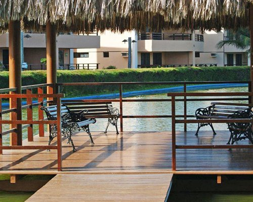A wooden pier leading to a patio on the water.