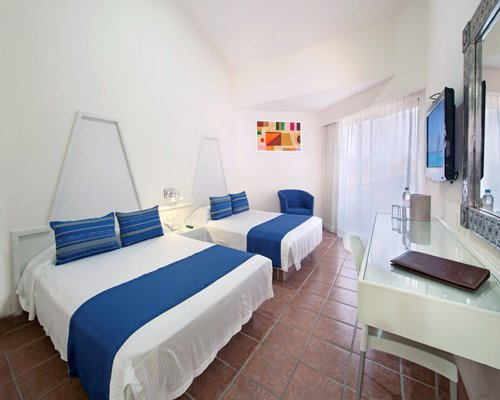 A well furnished bedroom with two beds and a television.