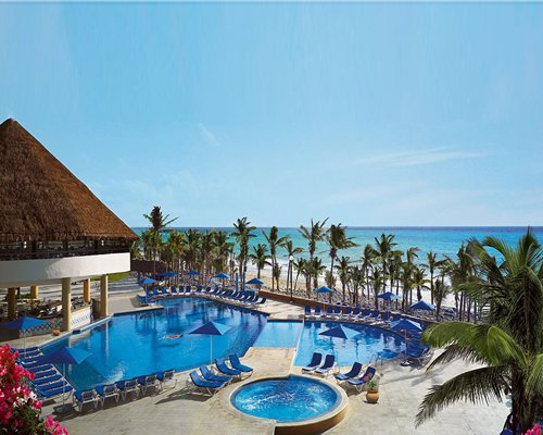 Outdoor swimming pool with a hot tub chaise lounge chairs sunshades and palm trees alongside the beach.