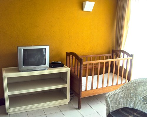 A living room with a television and infant bed.