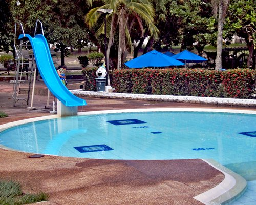 Outdoor swimming pool with slide and sunshades.