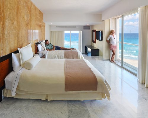 A well furnished bedroom with two beds and patio with an ocean view.