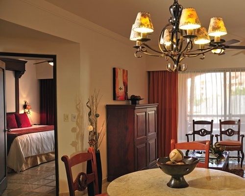 A well furnished dining room alongside a bedroom.