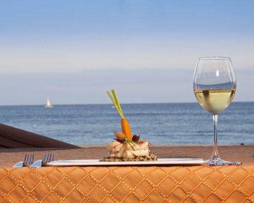 A food item on an outdoor table alongside the ocean.