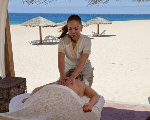 A man enjoying a massage alongside the beach.