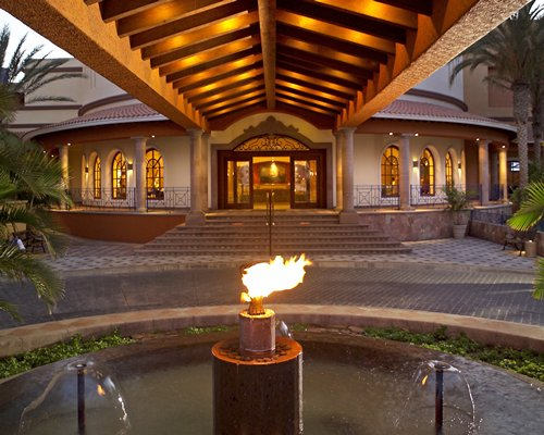 A view of the resort entrance alongside a torch with fire.