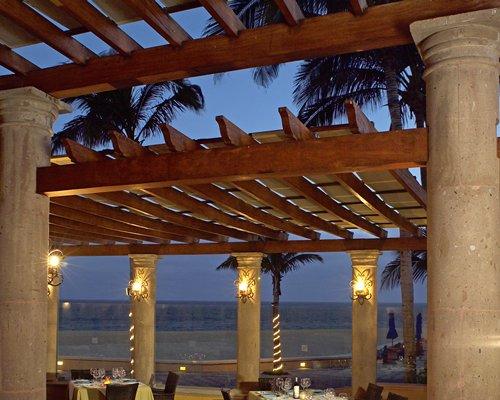 An outdoor fine dining restaurant alongside the ocean.