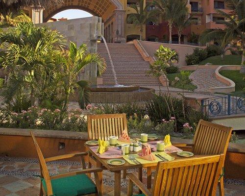 An outdoor fine dining restaurant alongside a water feature.