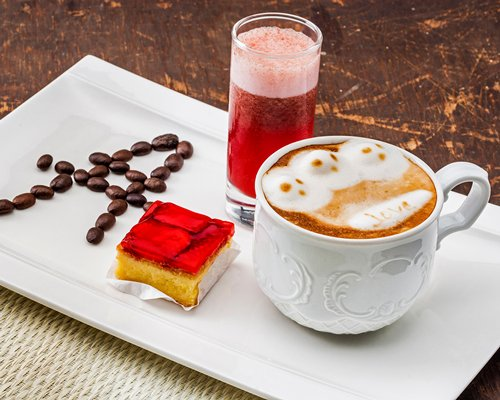 A view of coffee and pastry on a plate.