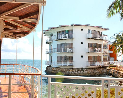 Exterior view of multiple unit balconies from a wooden pier alongside the sea.