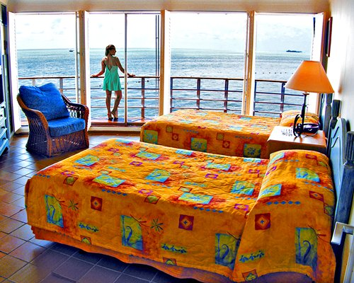A well furnished bedroom with two twin beds a women standing at the balcony with a view of the sea.