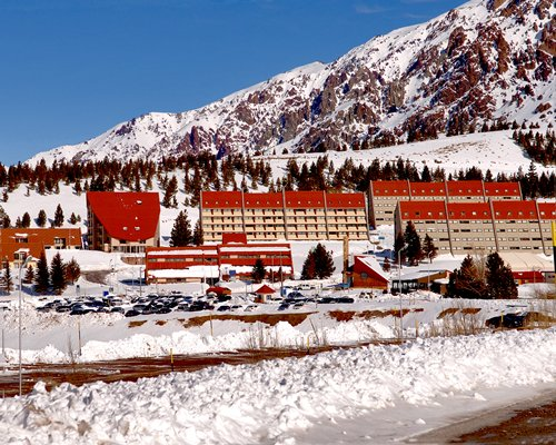 Exterior view of the Geminis Apart Hotel with parking lot alongside mountains covered in snow.