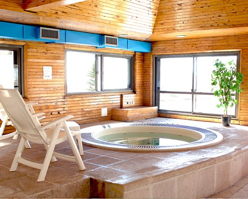An indoor hot tub with chaise lounge chairs and an outside view.