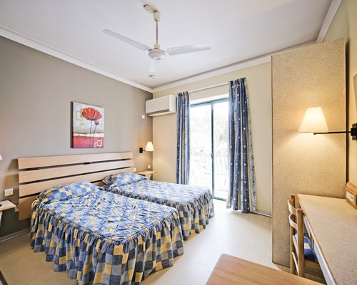 A well furnished bedroom with two twin beds and outdoor view.