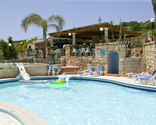 Outdoor swimming pool with chaise lounge chairs alongside a restaurant.