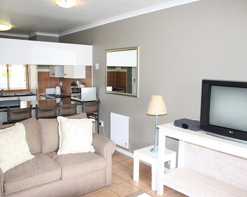 A well furnished living room with a television alongside the kitchen with a breakfast bar.