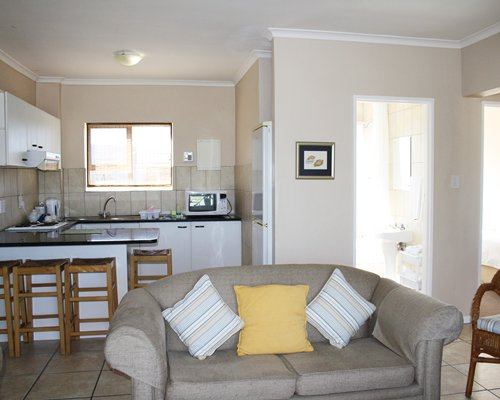 A well furnished living room with an open plan kitchen and breakfast bar.