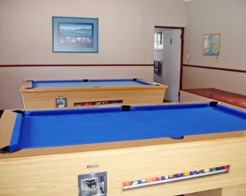 An indoor recreational room with pool tables.