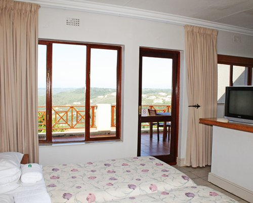 A well furnished bedroom with a twin bed television and balcony.