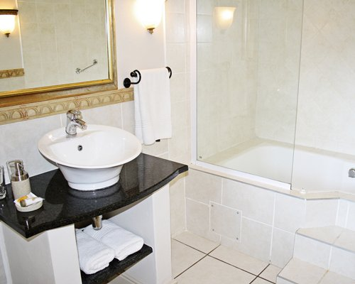 A bathroom with shower bathtub and sink.