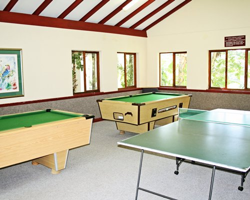 An indoor recreation room with ping pong and pool tables.