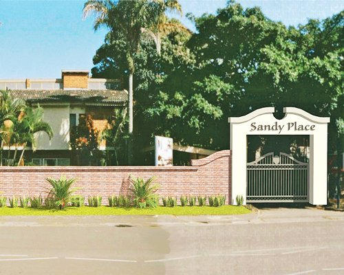 Scenic exterior view of Sandy Place surrounded by wooded area.
