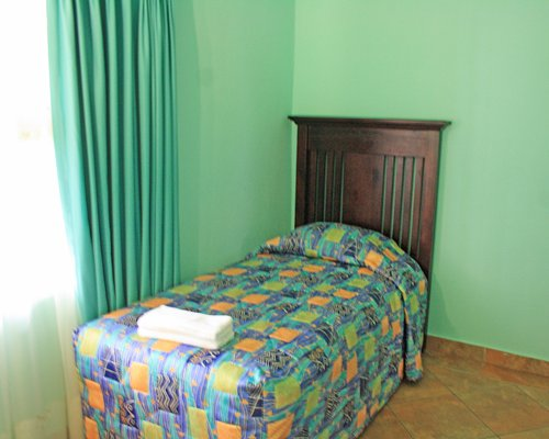 A well furnished bedroom with twin bed and outside view.