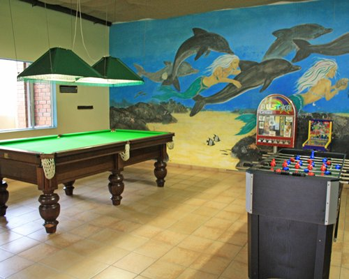 Indoor recreation room with pool table foosball and outside view.