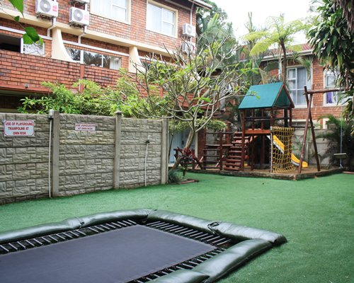 Outdoor recreation area with kids playscape and trampoline.