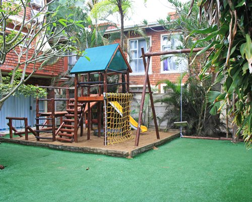 An outdoor kids playscape alongside resort units.