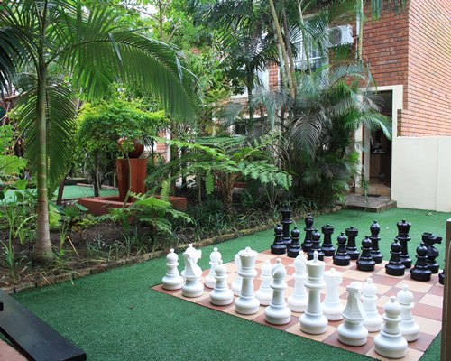 An exterior view of resort units alongside trees and a giant chess set.