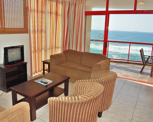 A well furnished living room with a television balcony and ocean view.