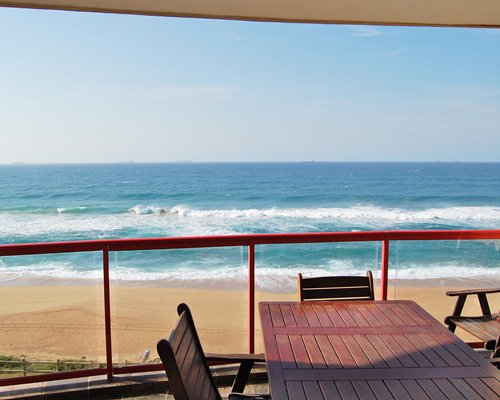 Balcony view of the beach with patio furniture.