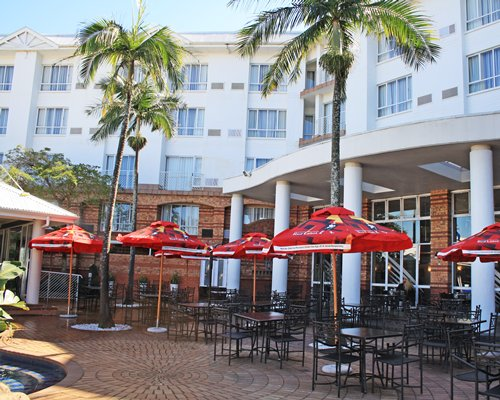 An outdoor dining area alongside multi story resort units.